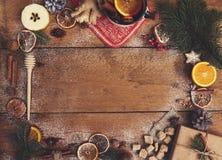 Vino reflexionado sobre en taza rústica con las especias y los ingredientes en de madera Imagenes de archivo