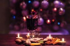 Vino reflexionado sobre en un fondo oscuro Nochebuena del invierno con las velas Imagen de archivo libre de regalías