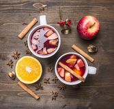 Vino reflexionado sobre fresco, hecho con la naranja y la manzana en una taza blanca, con el caramelo de la Navidad, la Navidad,  fotografía de archivo