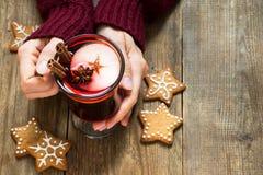 Vino reflexionado sobre la Navidad en manos femeninas imagen de archivo libre de regalías