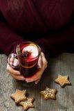 Vino reflexionado sobre la Navidad en manos femeninas fotografía de archivo