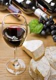 Vino rojo, brie, camembert y uva Fotos de archivo