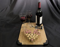 Vino rojo con las copas de vino y los corchos Fotos de archivo libres de regalías