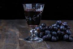 Vino rojo con las uvas en el lado Imagen de archivo libre de regalías