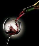 Vino rojo de colada de una botella en un vidrio Foto de archivo libre de regalías