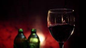 Vino rojo de colada en el tiroteo de cristal, fondo carmesí, atmósfera romántica durante la fecha, vídeo de alta calidad almacen de metraje de vídeo