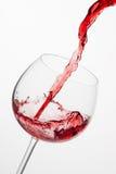 Vino rojo de colada en el vidrio. Foto de archivo libre de regalías