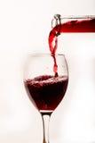 Vino rojo de colada en el vidrio Foto de archivo