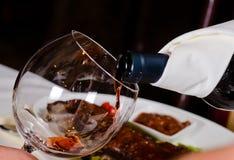 Vino rojo de colada en el vidrio Imagenes de archivo