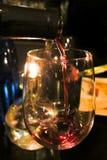 Vino rojo de colada en el vidrio de una botella Imagenes de archivo
