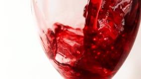 Vino rojo de colada en la copa contra el primer blanco del extremo del fondo Vinificación, color rojo y conceptos del sabor almacen de video