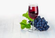 Vino rojo de cristal con las uvas del racimo Imagenes de archivo
