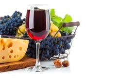 Vino rojo de cristal con las uvas y el queso Imágenes de archivo libres de regalías