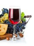 Vino rojo de cristal con las uvas y el queso Fotografía de archivo libre de regalías