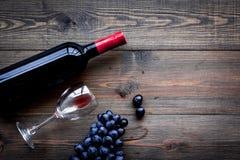 Vino rojo del gusto Botella de uva roja del vino, de cristal y negra en copyspace de madera oscuro de la opinión superior del fon fotografía de archivo