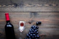 Vino rojo del gusto Botella de uva roja del vino, de cristal y negra en copyspace de madera oscuro de la opinión superior del fon foto de archivo libre de regalías