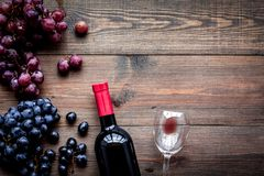 Vino rojo del gusto Botella de uva roja del vino, de cristal y negra en copyspace de madera oscuro de la opinión superior del fon fotografía de archivo libre de regalías