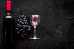 Vino rojo del gusto Botella de uva roja del vino, de cristal y negra en copyspace de piedra negro de la opinión superior del fond fotografía de archivo libre de regalías
