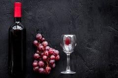 Vino rojo del gusto Botella de vino rojo, de vidrio y de uva roja en copyspace negro de la opinión superior del fondo fotografía de archivo