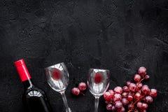 Vino rojo del gusto Botella de vino rojo, de vidrio y de uva roja en copyspace negro de la opinión superior del fondo fotos de archivo libres de regalías