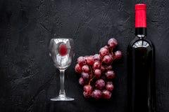 Vino rojo del gusto Botella de vino rojo, de vidrio y de uva roja en copyspace negro de la opinión superior del fondo foto de archivo libre de regalías