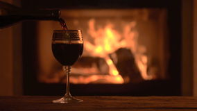 Vino rojo delicioso de colada en la chimenea romántica almacen de video