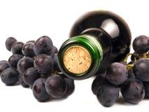 Vino rojo en botella y uvas Imágenes de archivo libres de regalías