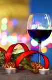 Vino rojo en decoraciones de un vidrio y de la Navidad con el fondo defocused Foto de archivo