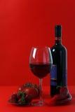Vino rojo en fondo rojo con rojo Fotos de archivo