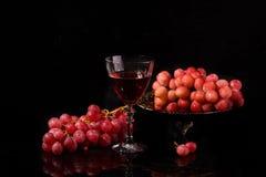 Vino rojo en uvas de cristal y rosadas en un fondo negro Imagenes de archivo