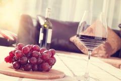 Vino rojo en vidrio con las uvas en la tabla Imagen de archivo libre de regalías