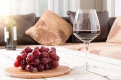 Vino rojo en vidrio con las uvas en la tabla Foto de archivo libre de regalías