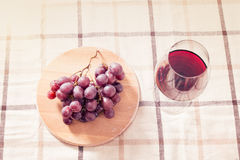 Vino rojo en vidrio con las uvas en la tabla Fotos de archivo libres de regalías