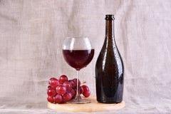 Vino rojo en vidrio y botella con las uvas en fondo de la materia textil Imagen de archivo