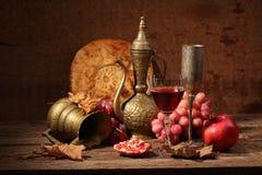 Vino rojo, granada jugosa, uvas dulces, torta plana y cobre Imágenes de archivo libres de regalías