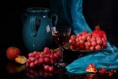 Vino rojo, jarro azul marino y fruta en un fondo negro Imagen de archivo libre de regalías