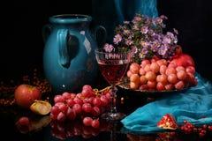 Vino rojo, jarro azul marino y fruta en un fondo negro Foto de archivo libre de regalías