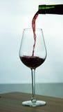 Vino rojo que cae en vidrio Imagen de archivo libre de regalías