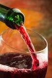 Vino rojo que es vertido en el vidrio Foto de archivo libre de regalías