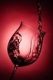 Vino rojo que es vertido en la copa de vino Imagen de archivo