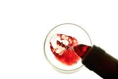 Vino rojo que es vertido en un vidrio aislado en blanco Foto de archivo libre de regalías