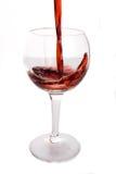 Vino rojo que es vertido en un vidrio de vino Imagenes de archivo