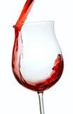 Vino rojo que es vertido en un vidrio de vino imagen de archivo
