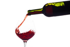 Vino rojo que es vertido en una copa de vino Fotografía de archivo libre de regalías