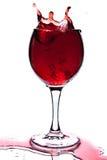 Vino rojo que salpica en el vidrio aislado Imagen de archivo libre de regalías