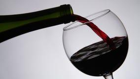 Vino rojo que vierte en el vidrio de vino Cierre para arriba metrajes