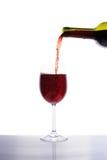 Vino rojo que vierte en la copa de vino Foto de archivo libre de regalías