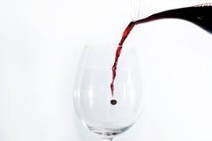 Vino rojo que vierte en un vidrio Imagen de archivo libre de regalías