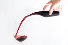 Vino rojo que vierte en un vidrio Imagen de archivo