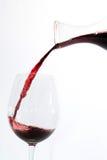 Vino rojo que vierte en un vidrio Imagenes de archivo